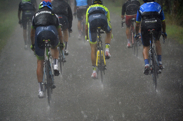Cyclists ride under a heavy rain during the 208.5 km nineteenth stage of the Tour de France cycling race.