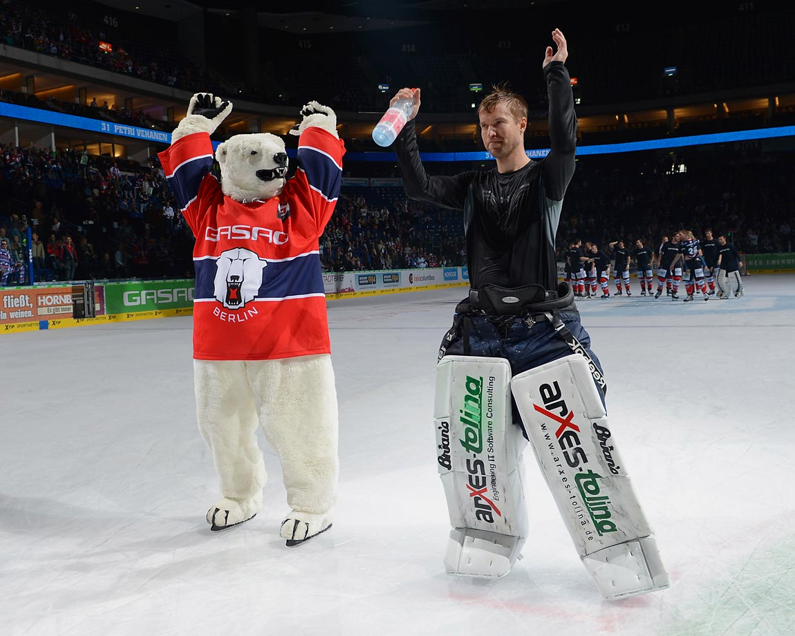 Mascot Bully and Petri Vehanen of Eisbaeren Berlin celebrate during the hockey game between Eisbaeren Berlin and Straubing Tigers.
