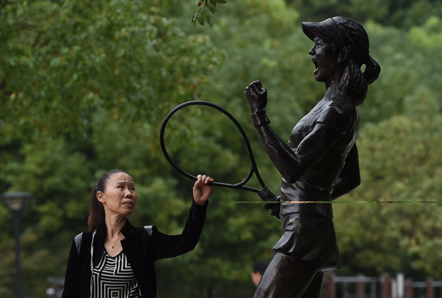 A woman reaches out to touch a statue of Chinese tennis star Li Na at a park in Wuhan, her hometown, in China's Hubei province.