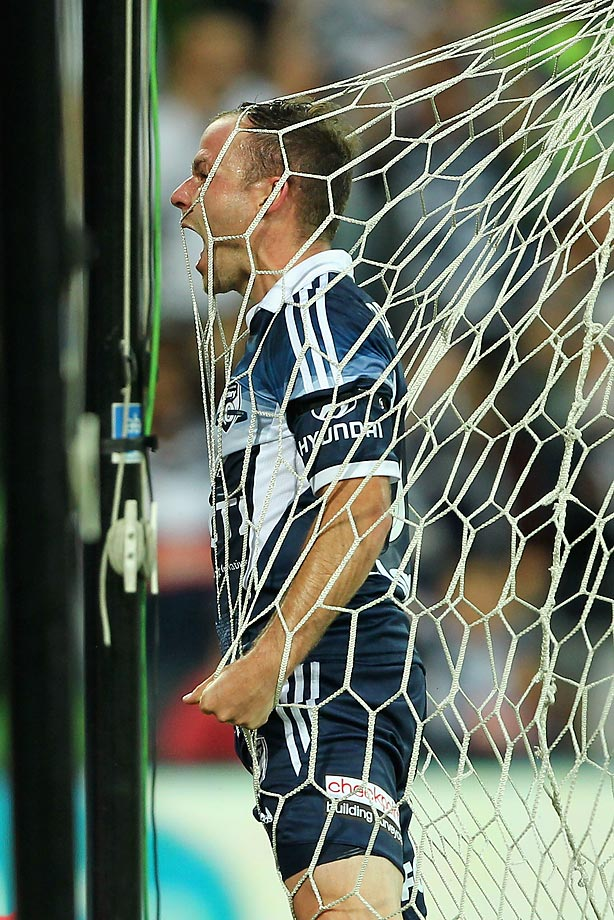 Leigh Broxham of Victory tests the strength of the net after scoring a goal against Adelaide United.