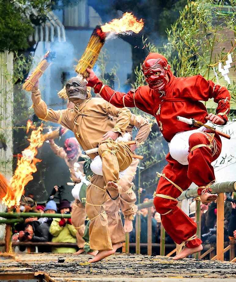 Some form of sumo wresting?  Men wearing ogre masks and costumes holding flaming torches dance during the Koshiki Tsuinashiki ritual, at Nagata Shrine in Japan.