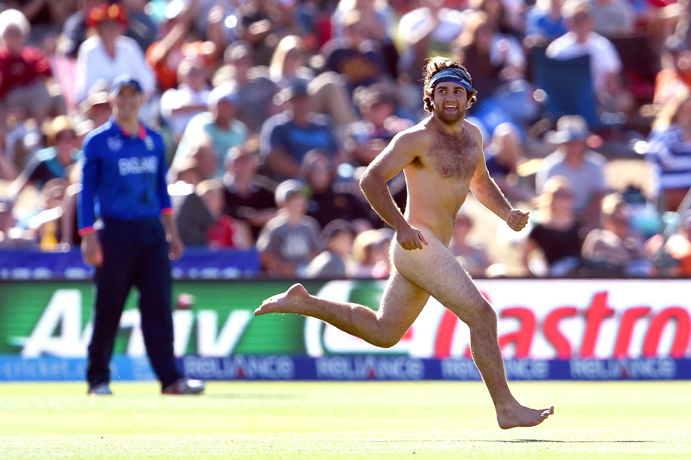 A streaker runs past an England player during the 2015 Cricket World Cup Group A match against Scotland in Christchurch.