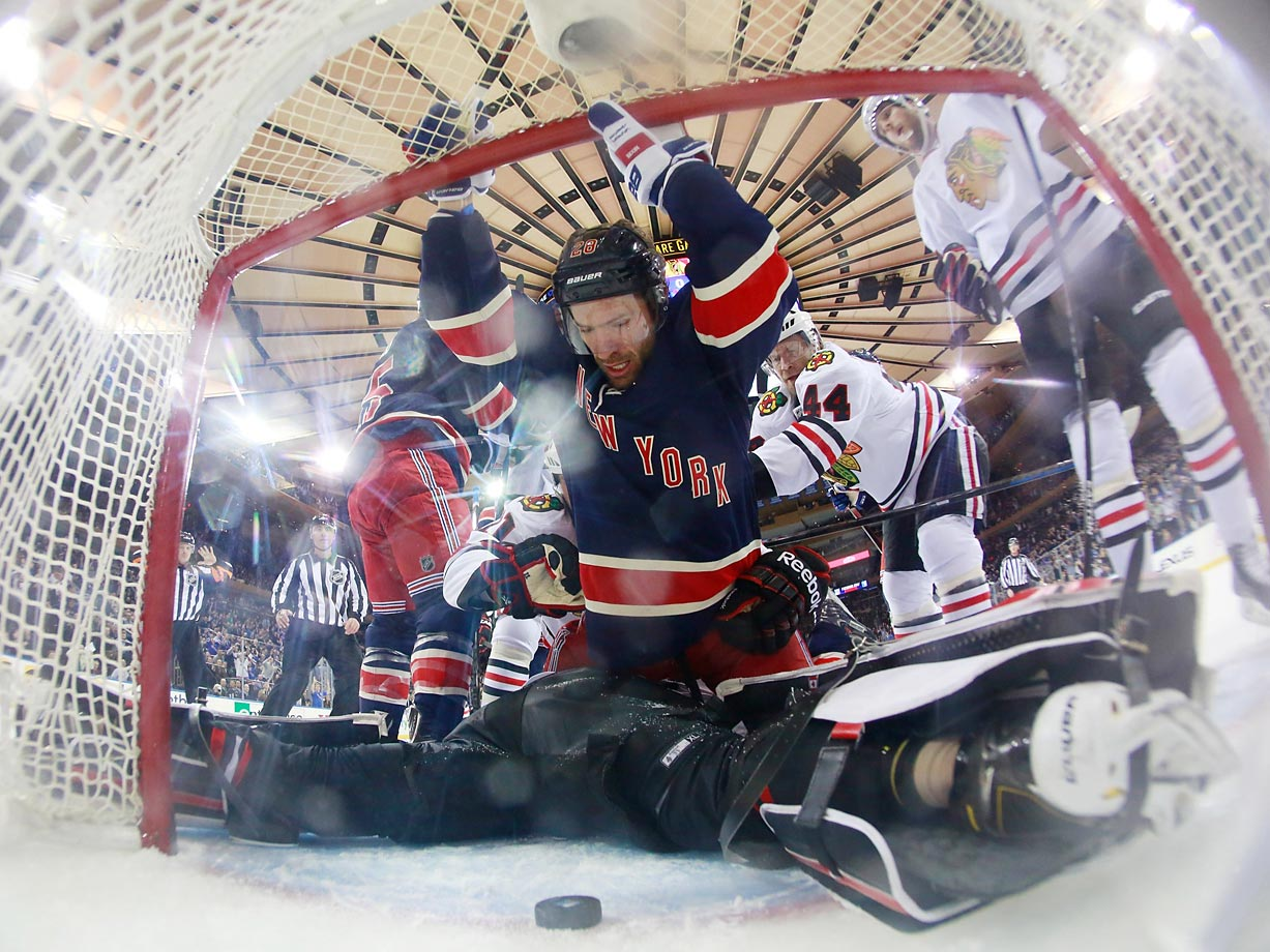 Dominic Moore of the New York Rangers falls into the net after getting hit from behind by Kimmo Timonen of the Chicago Blackhawks at Madison Square Garden.