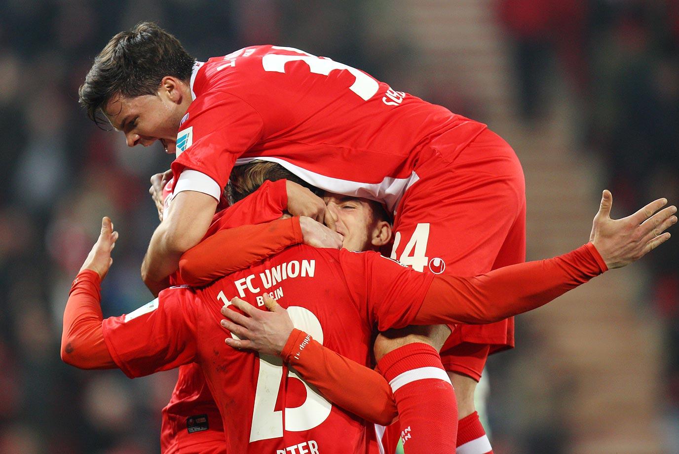 Sebastian Polter, Valmir Sulejmani and Fabian Schoenheim of 1 FC Union Berlin celebrate during a match against FC St. Pauli.