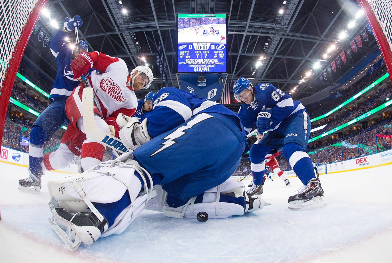 Goaile Ben Bishop of the Tampa Bay Lightning attempts to cover the puck as teammates Mark Barberio  and Andrej Sustr battle against Joakim Andersson of the Detroit Red Wings.