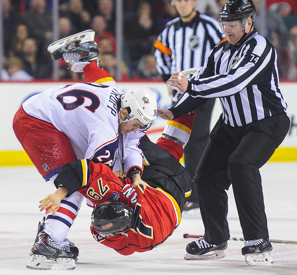 Michael Ferland of the Calgary Flames gets thrown during a fight against Corey Tropp of the Columbus Blue Jackets.