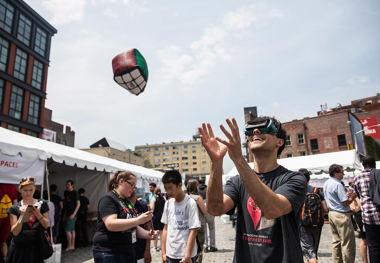 Michael Zaytsev attempts to catch a toy while wearing goggles that invert vision at Geek Street Fair in the Meat Packing District neighborhood of New York City.