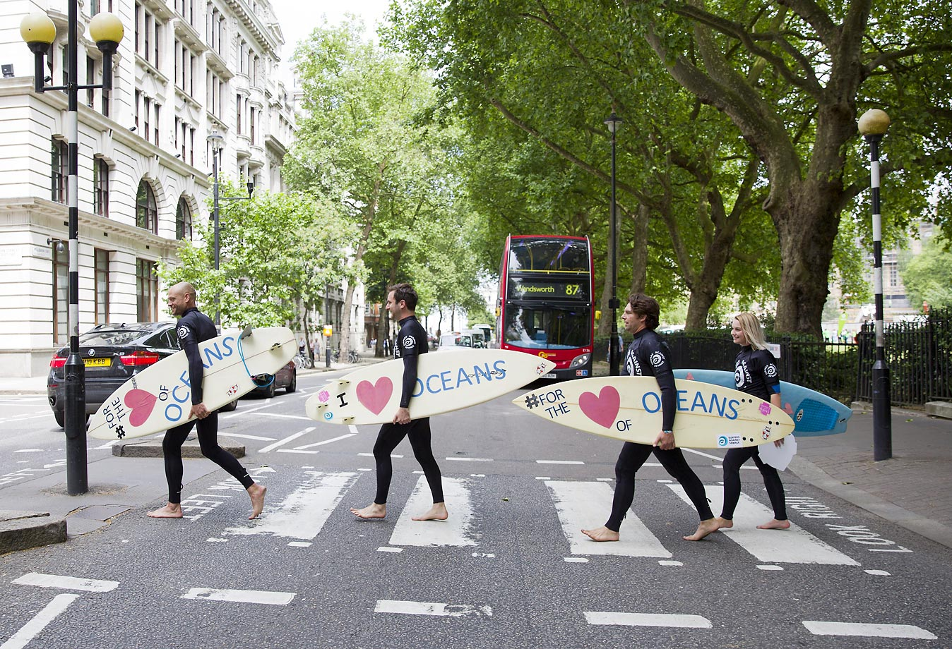 Climate change campaigners in wetsuits holding surfboards cross the road by the Houses of Parliament in London.