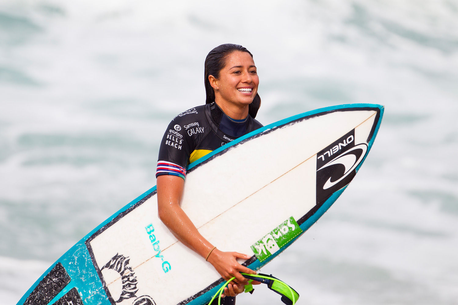 Malia Manuel of Hawaii walks with her surfboard after coming in second place in the first heat with a 14.03.