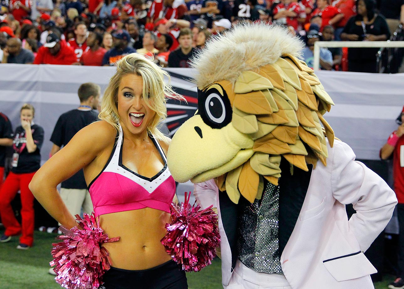 An Atlanta Falcons cheerleaders performs with mascot Freddie Falcon.