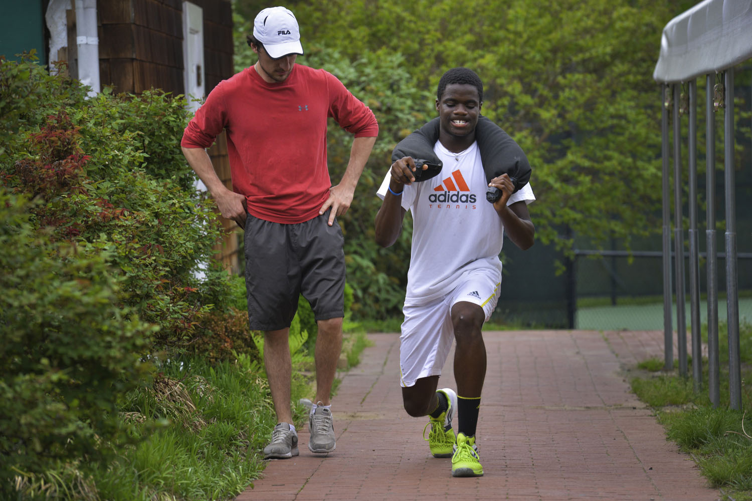 Under the watchful eyes of assistant fitness director T. C. Costello, Francis Tiafoe does weighted-lunges at the Junior Tennis Champions Center on May 9, 2014, in College Park, Maryland.