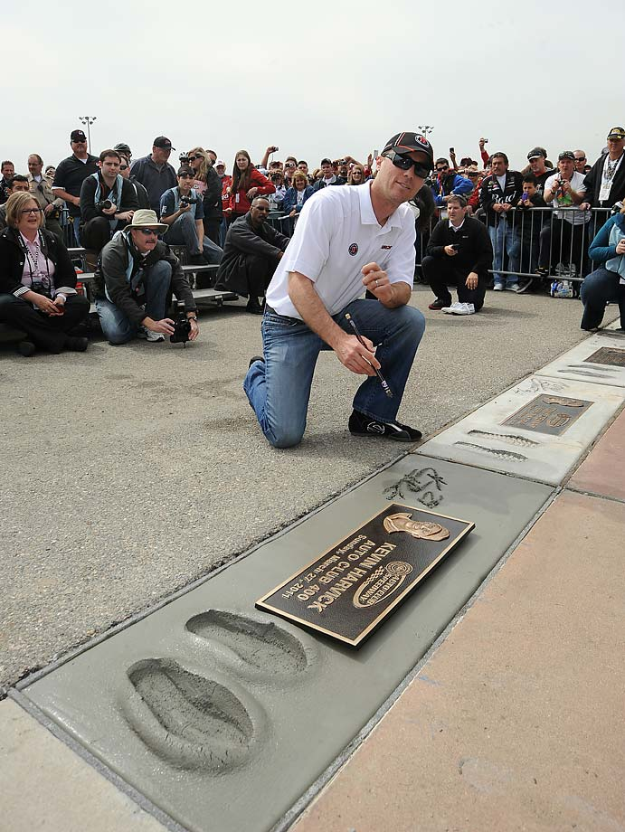 Kevin Harvick signs his name in concrete next to his plaque and foot prints on the walk of fame honoring his victory the previous year (2013) at Auto Club 400 in Fontana.