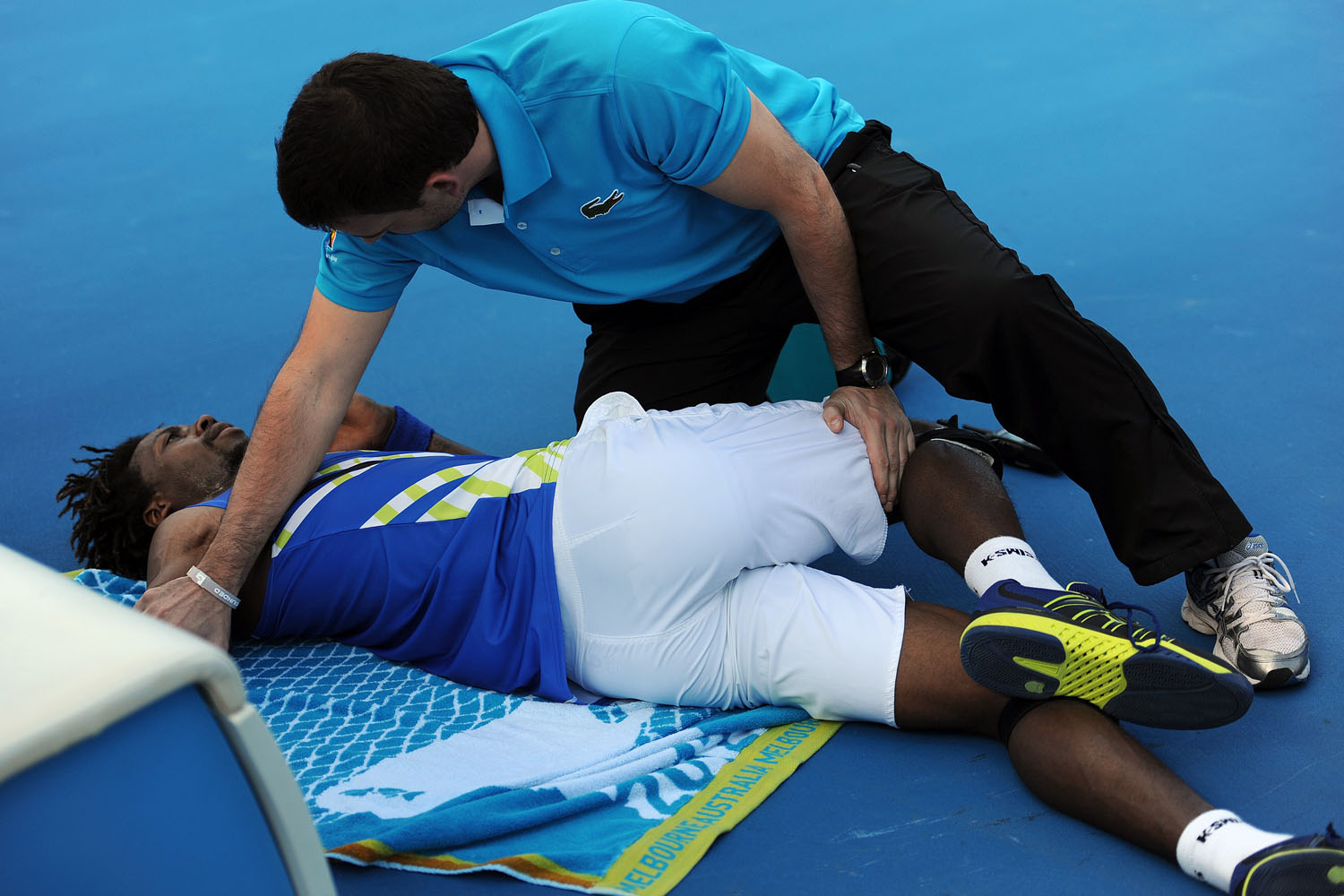 A physiologist works on Gael Monfils during a medical timeout in the break against Mikhail Kukushkin of Kazakhstan in their third round men's singles match at the 2012 Australian Open.