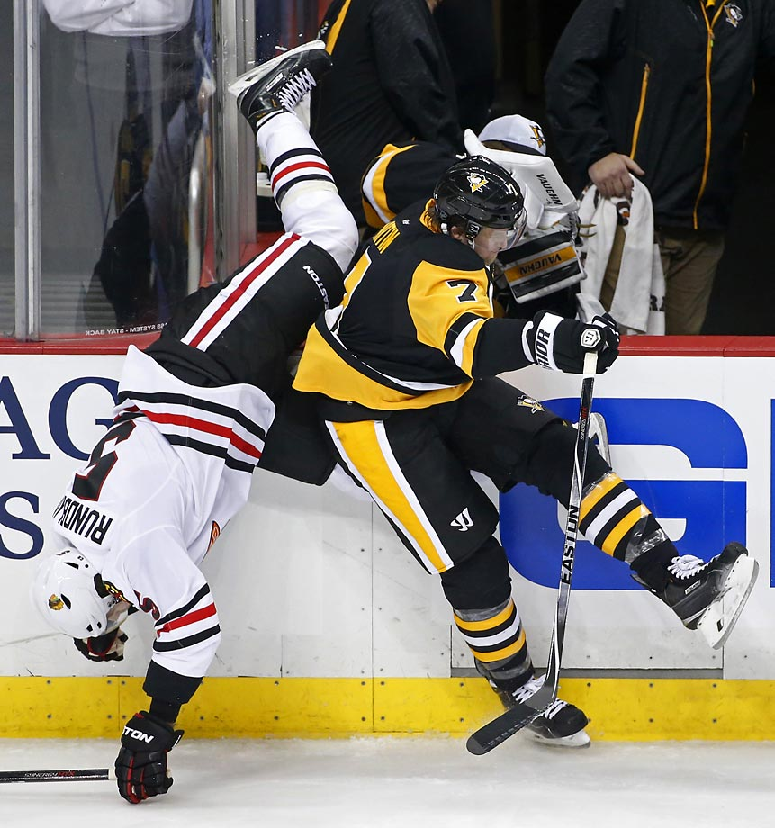 Paul Martin of the Penguins upends David Rundblad. The Blackhawks won in a shootout, 3-2.