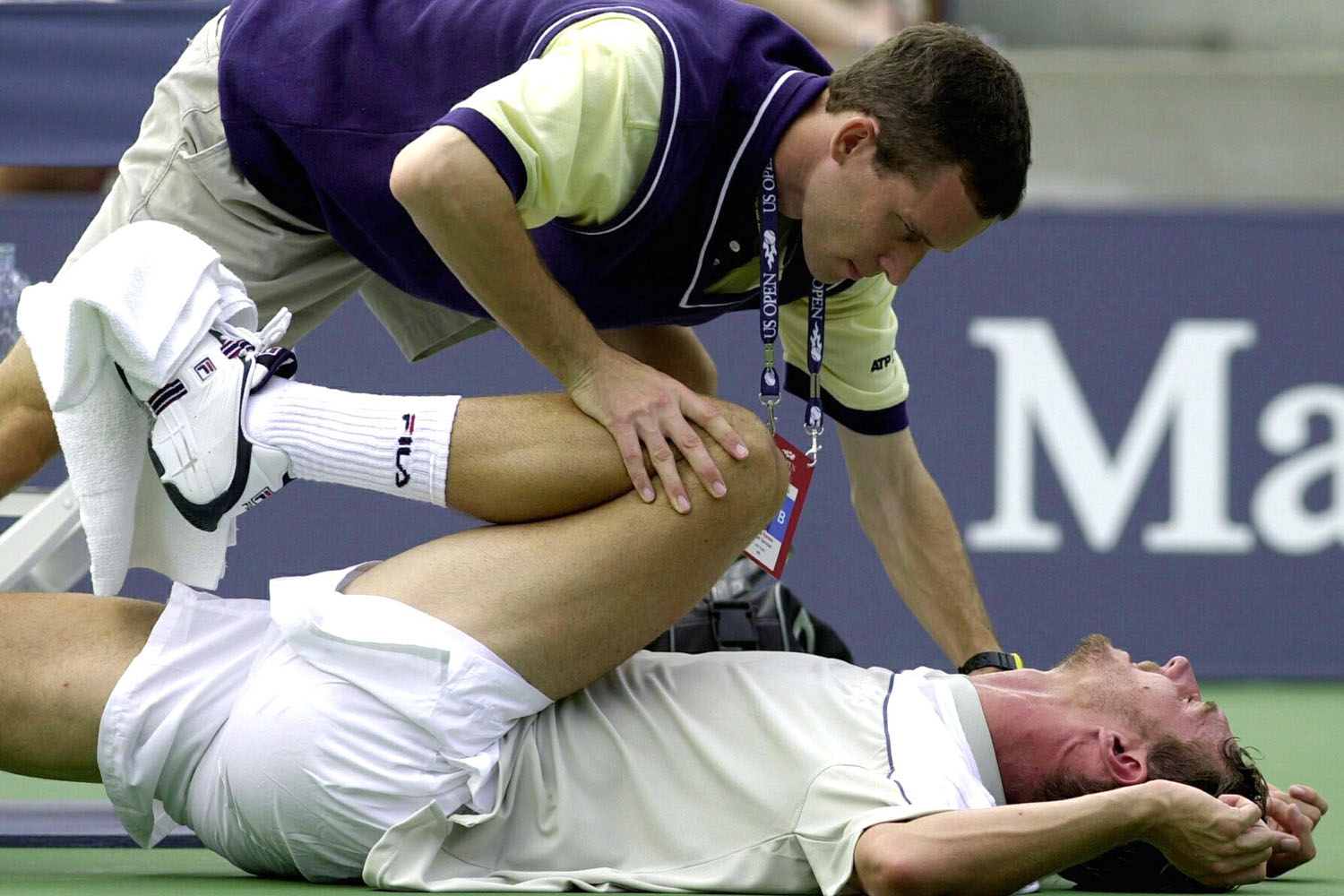 Julien Boutter has his leg stretched by a trainer during his match against number nine seeded Lleyton Hewitt at the US Open Tennis Tournament in Flushing Meadows, NY in 2000.