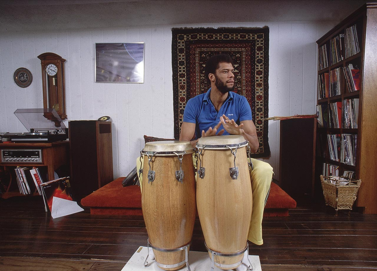 En route to his sixth MVP award in 1980, Kareem Abdul-Jabbar keeps loose by jamming on conga drums in his Bel Air home.