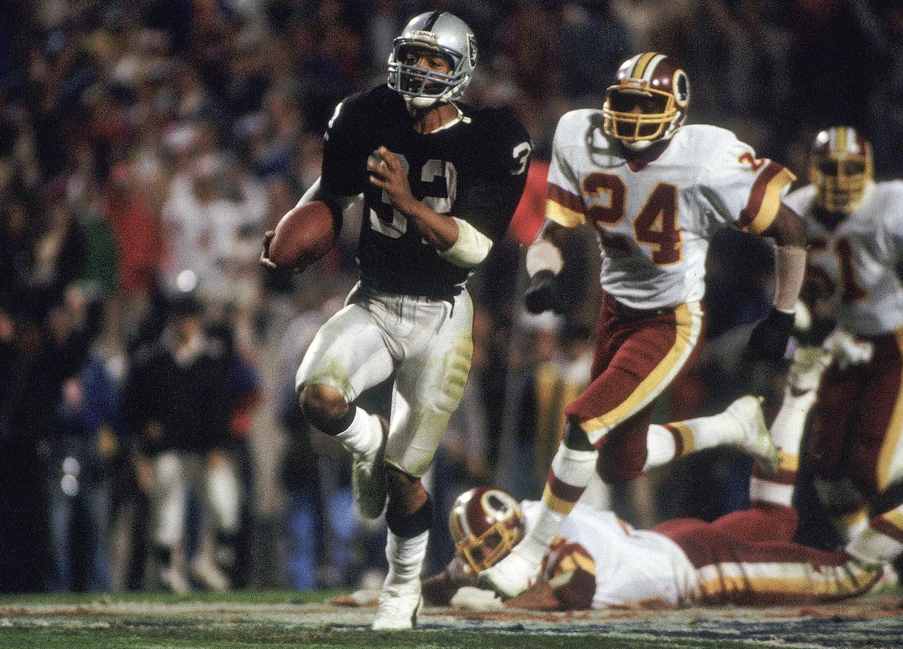 Los Angeles Raiders running back Marcus Allen races away from Anthony Washington and the rest of the Washington Redskins defense for a 74-yard touchdown in the third quarter of a 38-9 blowout. Allen's run was the longest in Super Bowl history at the time.