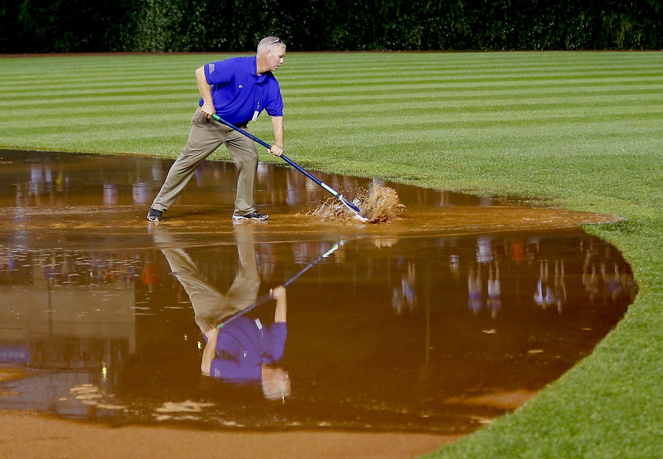 A member of the grounds crew has his hands full after a heavy rain soaked Wrigley Field on Tuesday.
