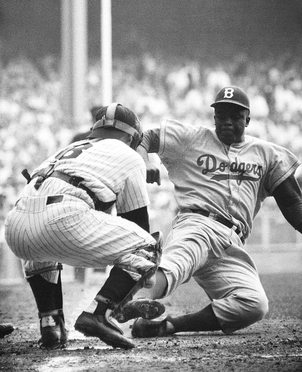World Series Game 1, Sept. 28, 1955 | Brooklyn Dodgers second baseman Jackie Robinson steals home against the New York Yankees in the eighth inning of Game 1 of the 1955 World Series. Despite Robinson's steal, the Dodgers lost the game 6-5, but they would go on to win the Series in seven games.