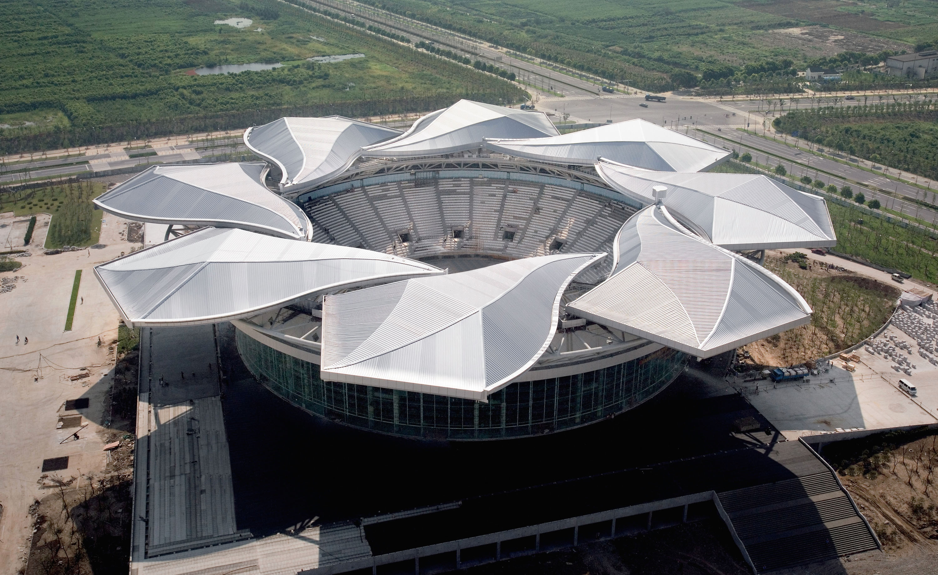 The Qizhong Tennis Center was built with a dual-purpose indoor-outdoor 15,000-seat center court and a special roof shaped like a magnolia flower, which can open and close like a lens shutter.