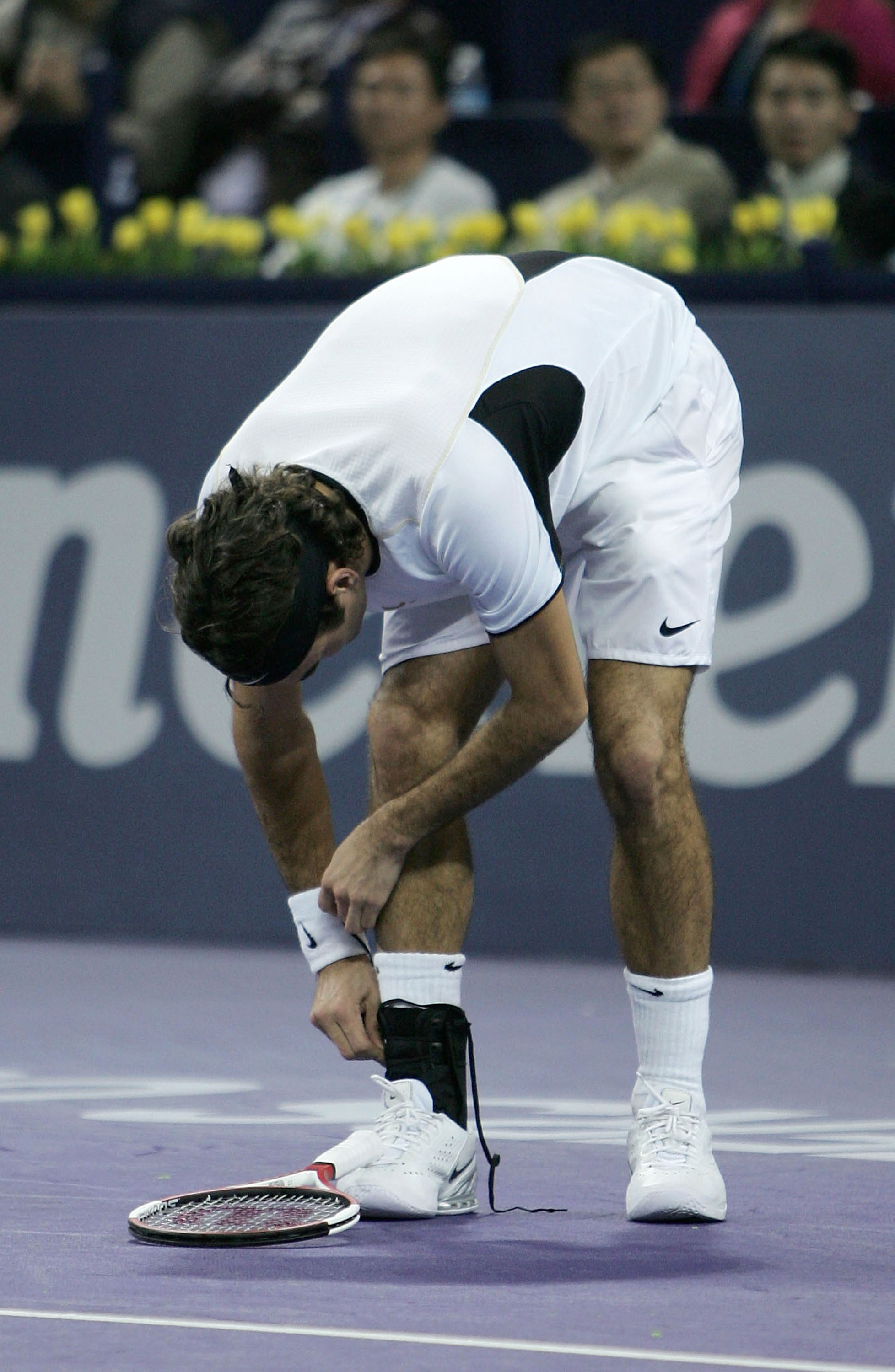 Federer of Switzerland re-straps his ankle during his five set match against Nalbandian.