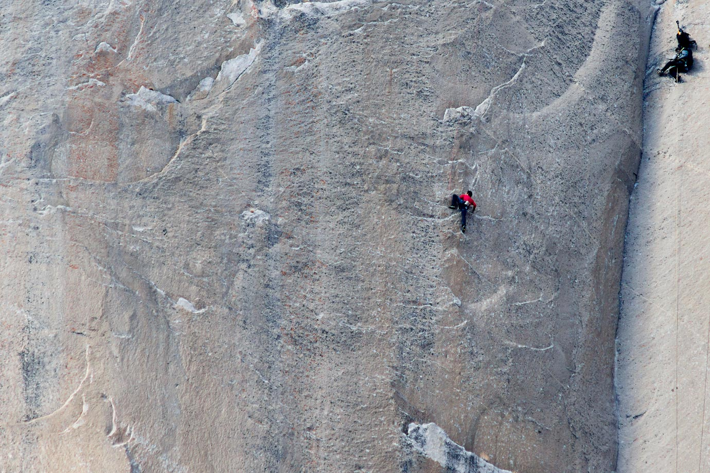 Kevin Jorgeson (in red) climbing on Pitch 18 while a cameraman (in blue, top right) shoots the action.