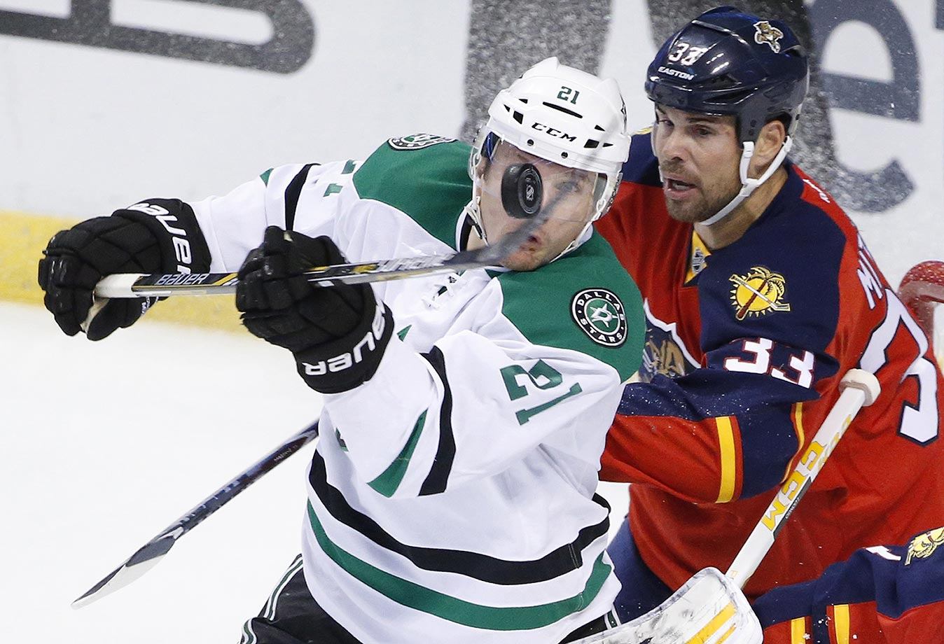 Antoine Roussel of the Dallas Stars bats the puck away from Willie Mitchell of the Florida Panthers.