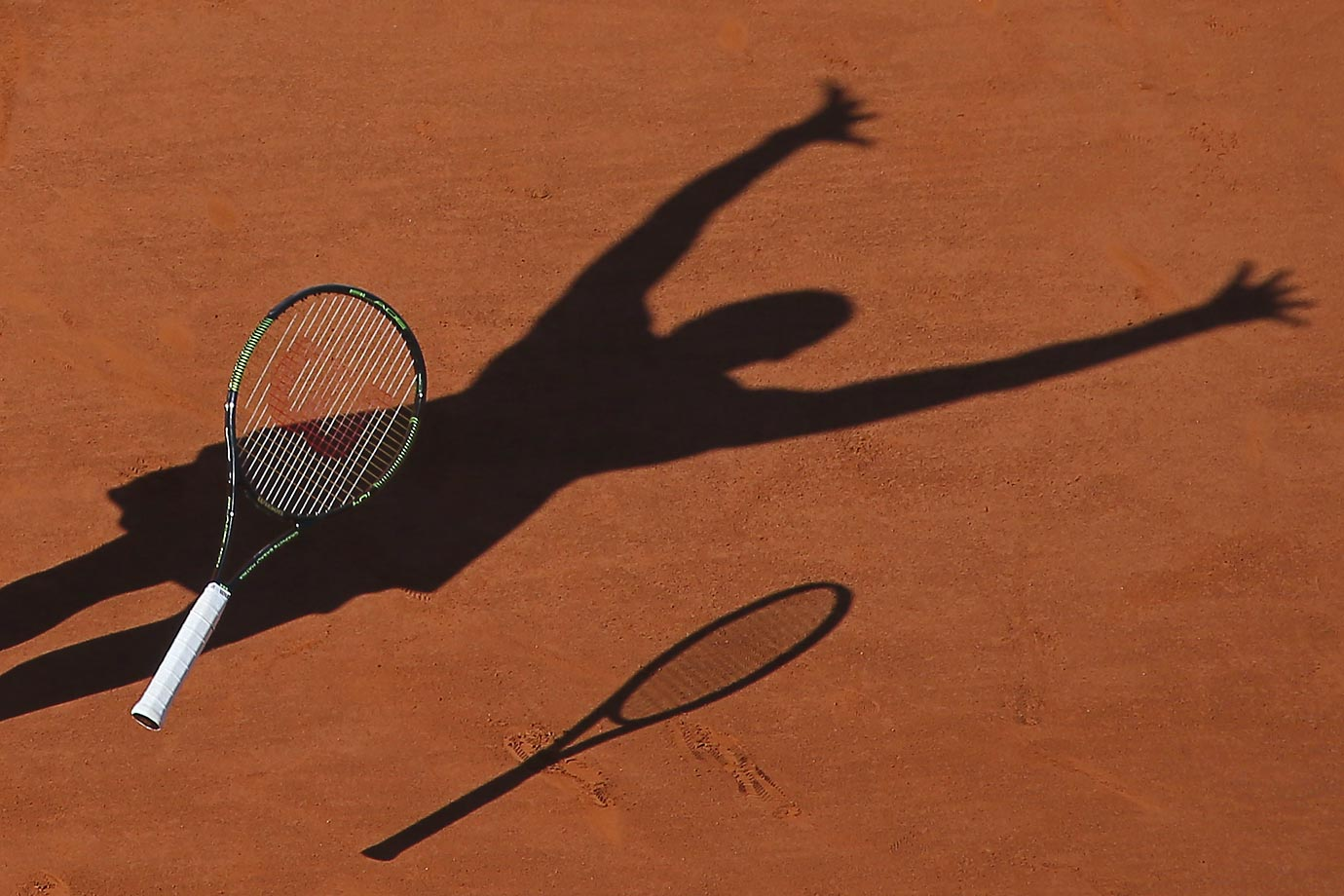 Seen through a shadow on the clay at the Roland Garros stadium in Paris is a victorious Serena Williams, who dropped her racket in celebration after beating Lucie Safarova in three sets, 6-3, 6-7, 6-2, to win the French Open on June 6.