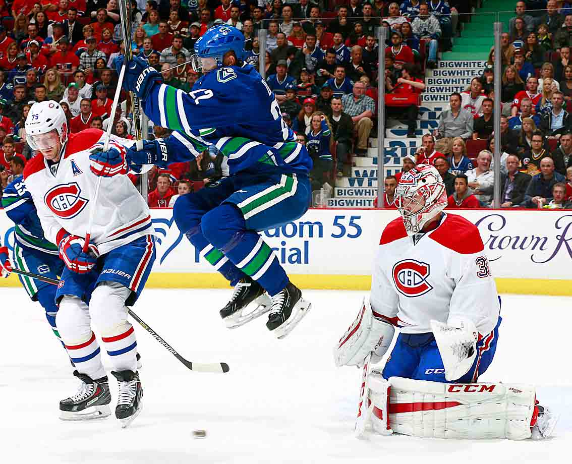 Vancouver's Daniel Sedin sails between Montreal defenseman Andrei Markov and goalie Carey Price to avoid a shot at Rogers Arena on October 30, 2014.