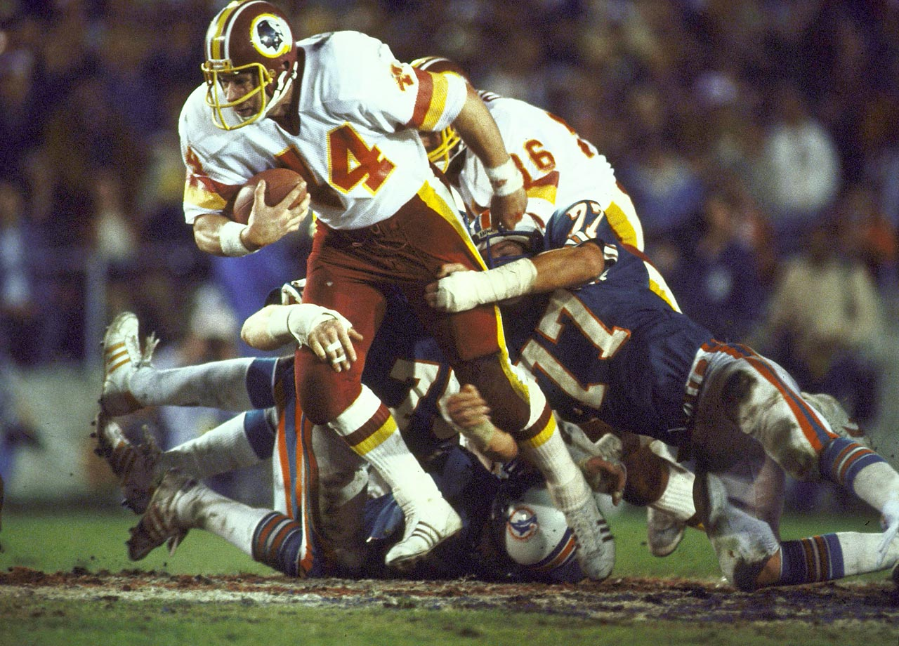 Washington Redskins running back John Riggins powers his way through Miami Dolphins tacklers. Riggins outgained the entire Miami offense with 181 total yards, 166 of them on the ground in the 27-17 win. With his team trailing 17-13 in the fourth quarter, Riggins came up huge on a crucial fourth-and-one, taking the ball 43 yards to the end zone.