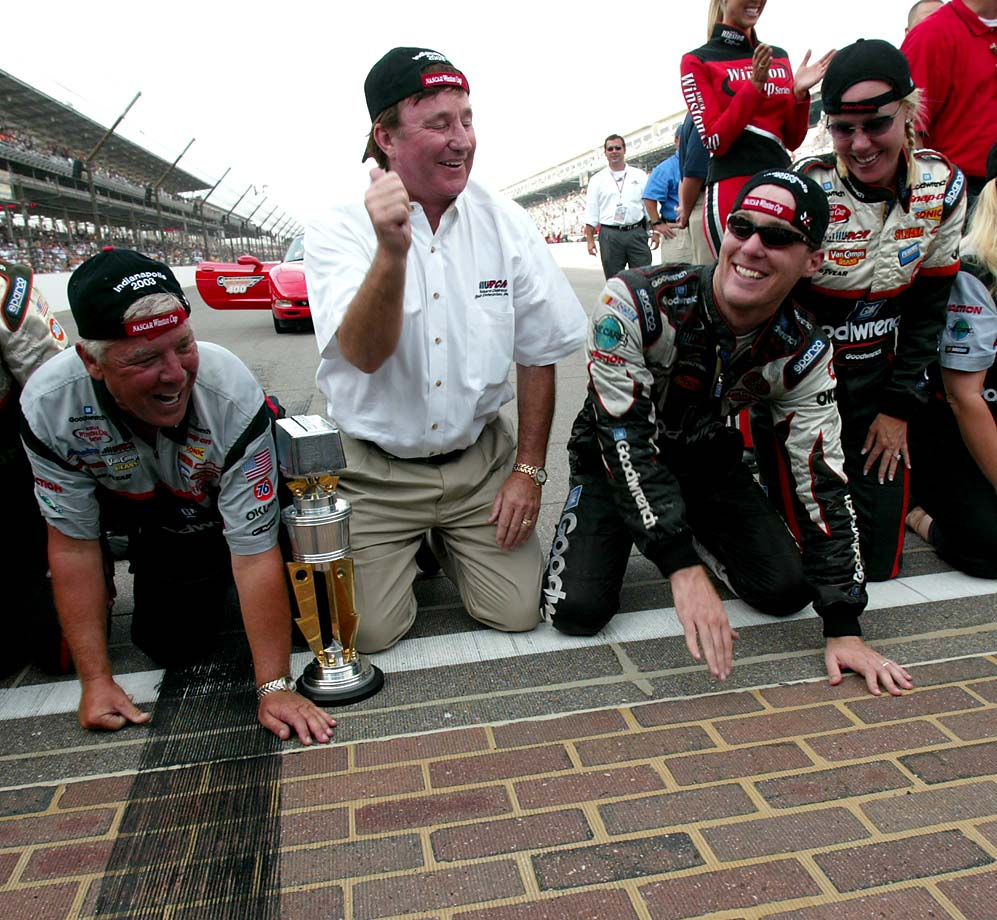 Kevin Harvick prepares to kiss the famous yard-wide brick finish line after winning the Brickyard 400 at Indianapolis Motor Speedway in 2003. To Harvick's left is his wife, Delana, and to his right is car owner Richard Childress.