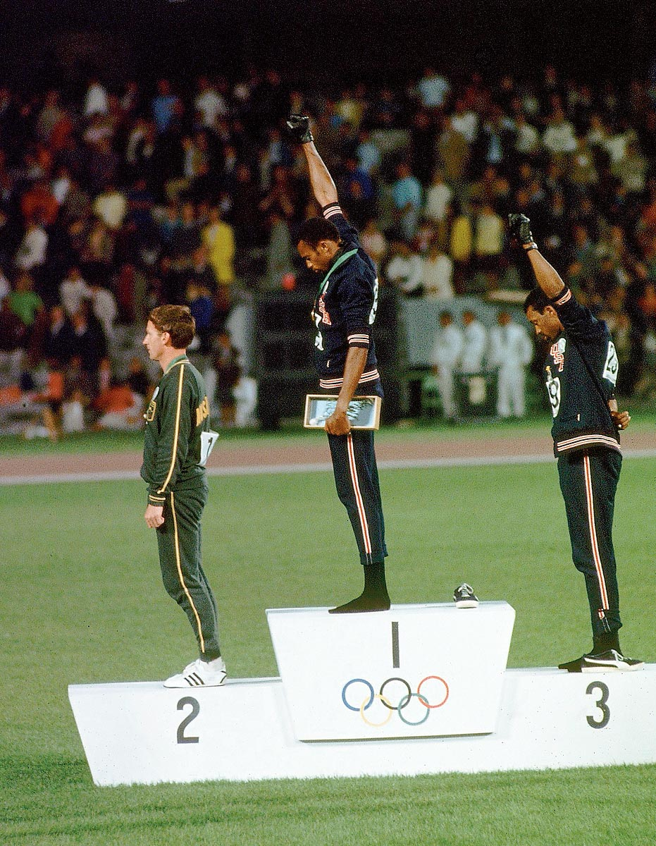 Summer Olympics, Oct. 16, 1968 | American sprinters Tommie Smith (center) and John Carlos (right) raise their black-gloved fists on the Olympic medal podium in Mexico City to signify Black Power. Smith, the gold medalist in the 200-meter race, and Carlos, the bronze medalist, were kicked out of the Games for their overtly political statement.