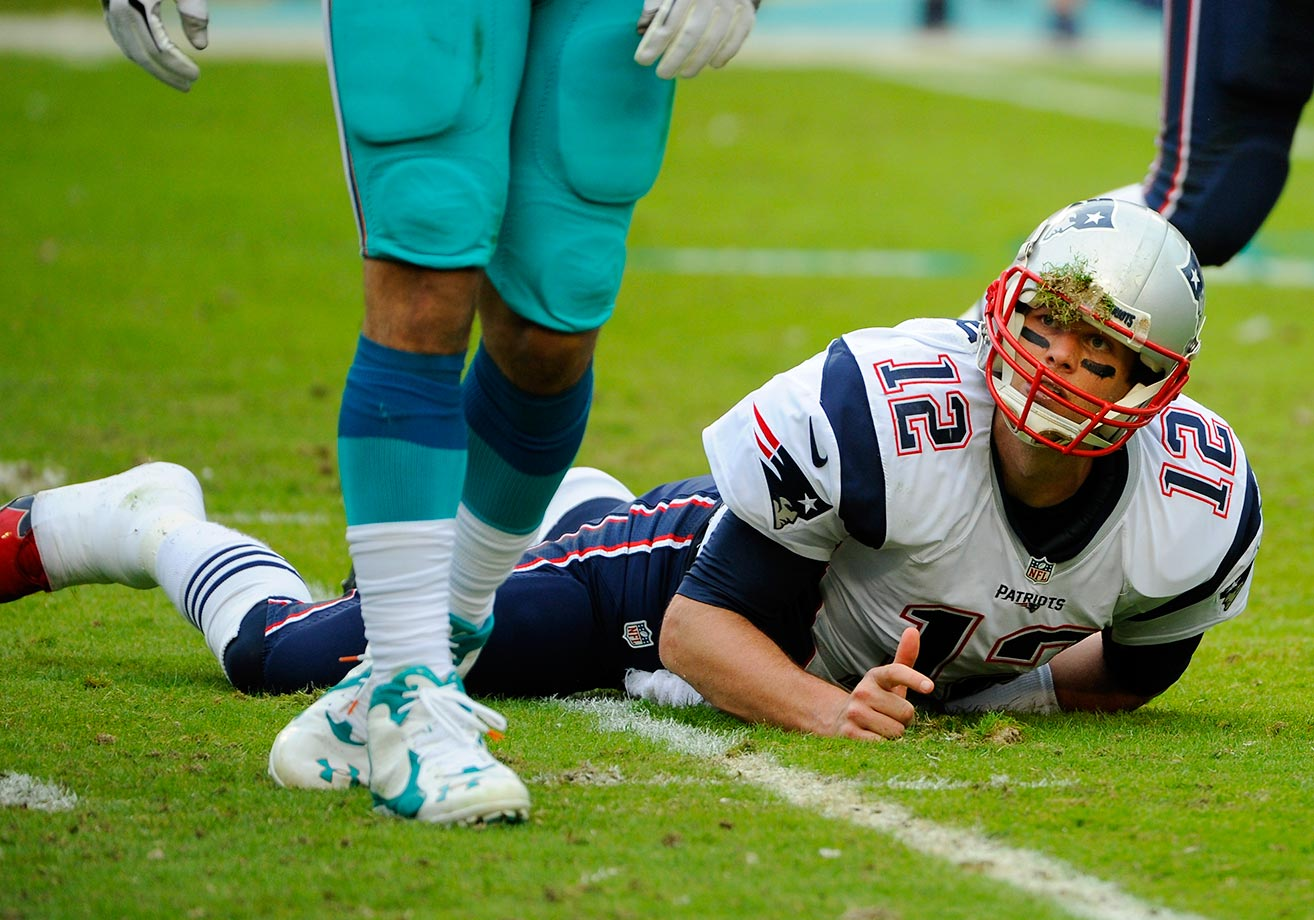 Tom Brady looks up at Olivier Vernon of the Miami Dolphins, who knocked him down.