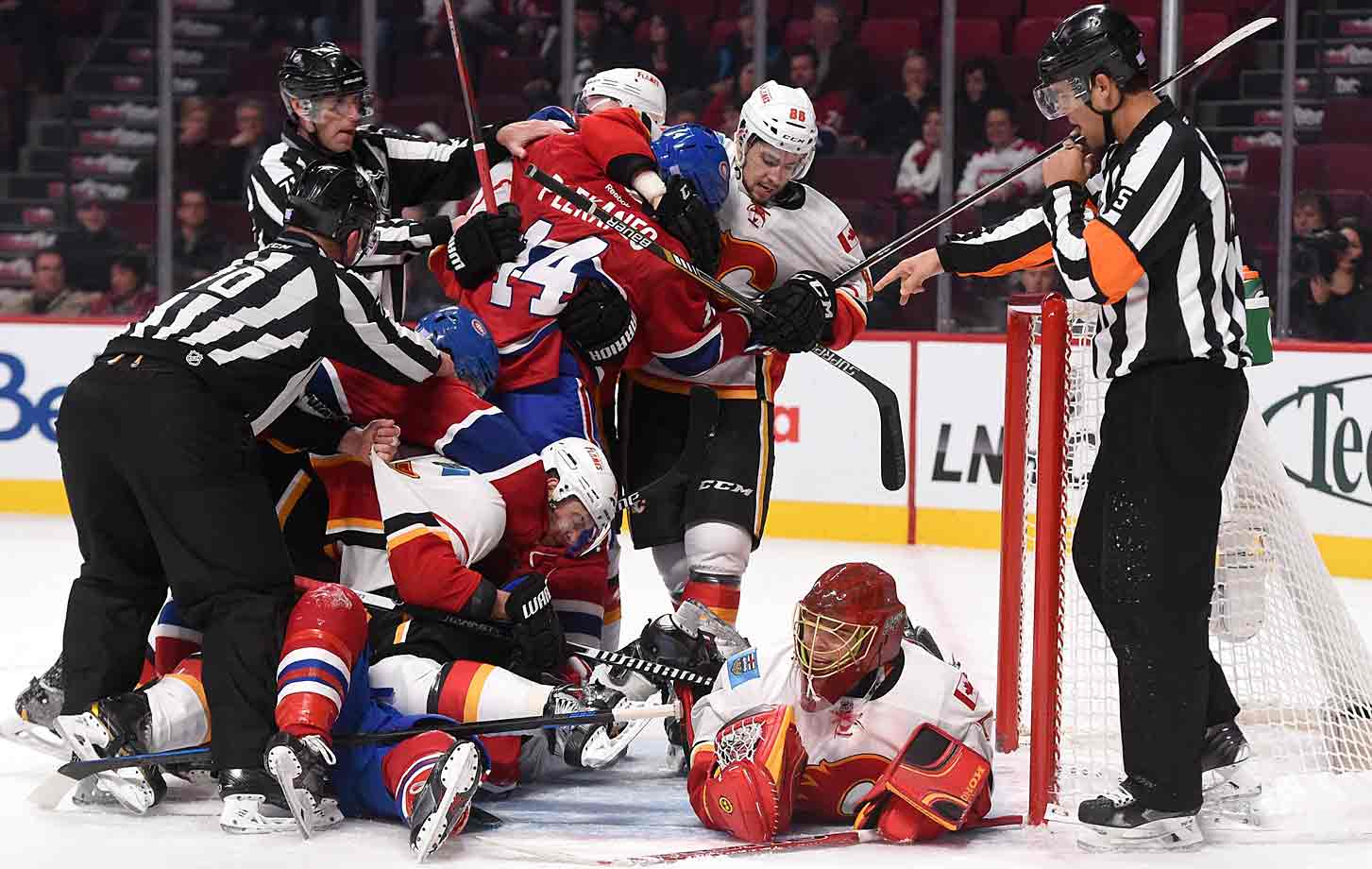 The Flames and Canadiens converge as Calgary netminder Jonas Hiller looks to exit the scrum, with puck in tow, at the Bell Centre in Montreal on November 2, 2014.