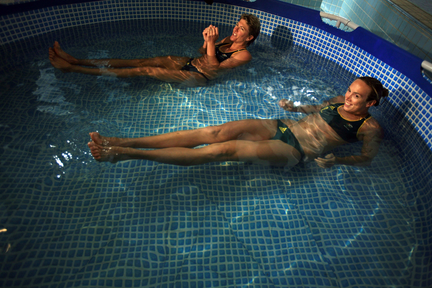Australian Olympic Beach Volleyball players Natalie Cook (L) and Tamsin Barnett (R) endure a plunge in the ice bath at the Fitness First Recovery Centre at the Western Academy of Beijing.