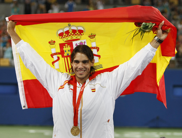 Nadal holds up the Spanish flag on the podium after receiving the gold medal.