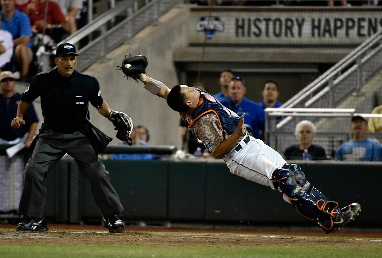 Matt Thaiss of Virginia loses his footing in a College World Series game against Vanderbilt.