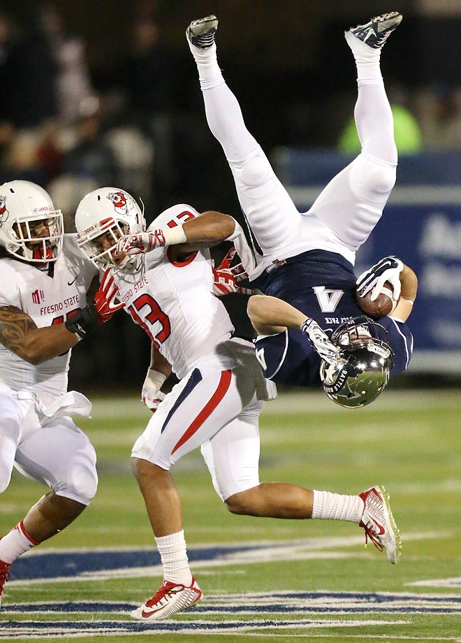 Nevada's Kendall Brock takes a tumble after making a catch against Fresno State's Derron Smith and Karl Mickelsen.