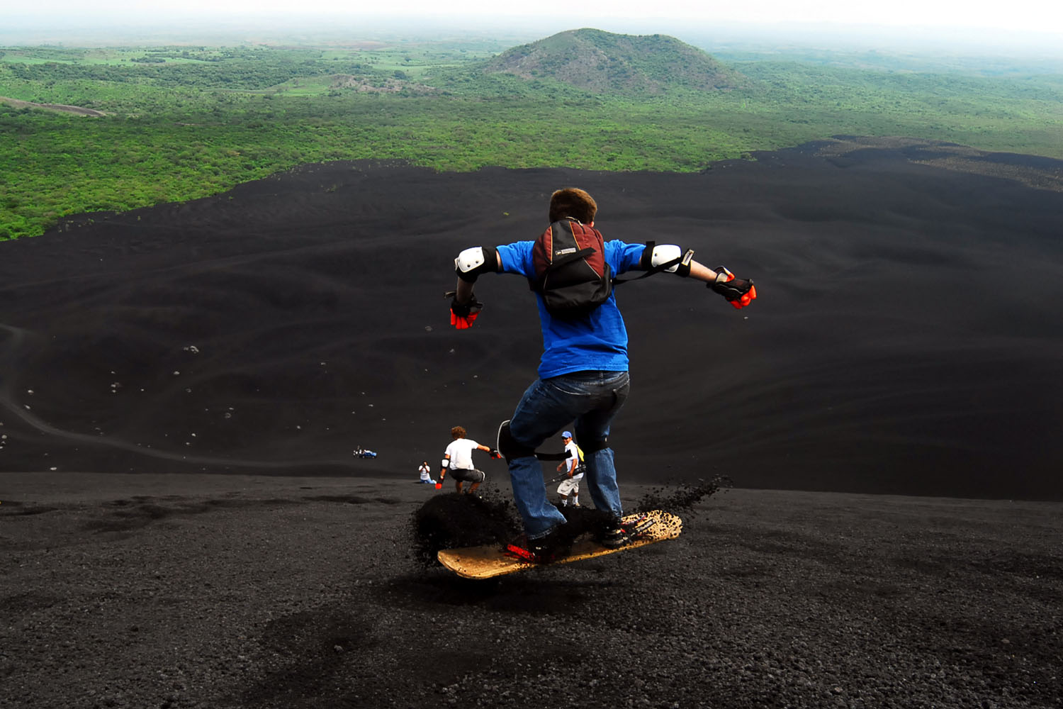 Tourists slide down the Cerro Negro volcano in the outskirts of Leon, Nicaragua.