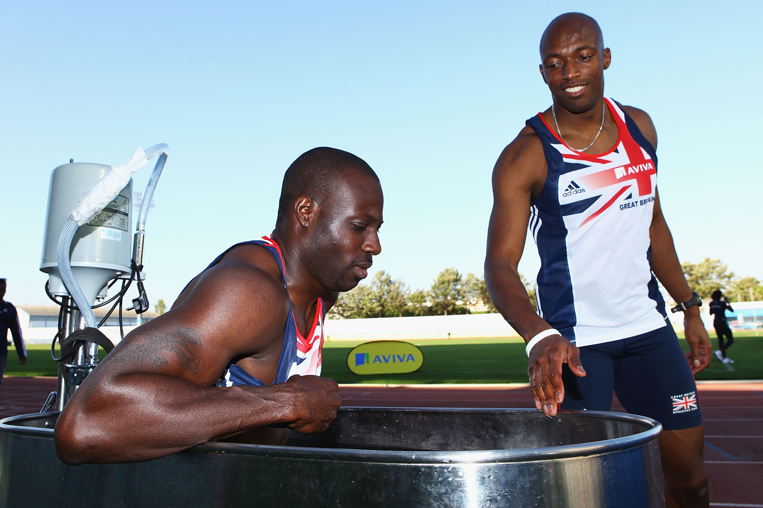 Tyrone Edgar (R) looks on as his teammate Marlon Devonish (L) dips into an ice bath during a training session at the Aviva GB & NI Team Preparation Camp.