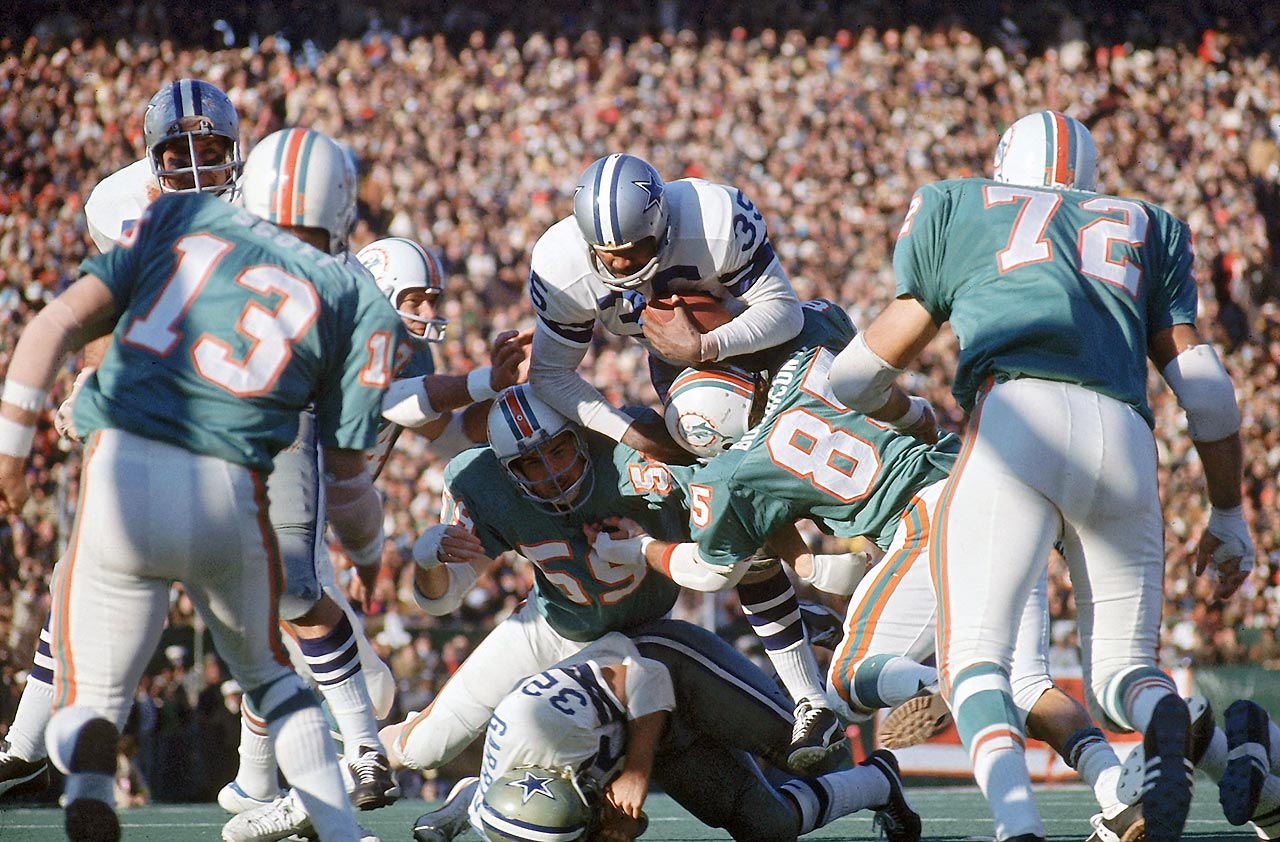 Dallas Cowboys running back Calvin Hill attempts to leap over the pile but gets tackled by the Miami Dolphins defense. The Cowboys dominated on the ground, rushing for a Super Bowl-record 252 yards en route to a 24-3 victory.