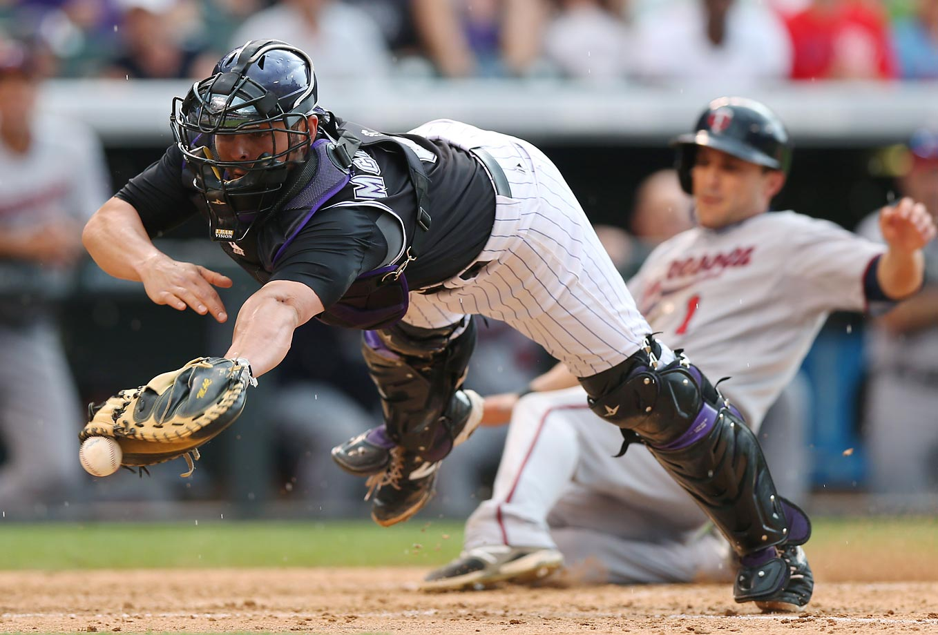 Colorado Rockies catcher Michael McKenry dives to field a throw from the outfield as Minnesota Twins outfielder Sam Fuld scores on a single by Chris Parmelee in the eighth inning of the Twins' 9-3 victory at Coors Field in Denver, Colorado, on July 12, 2014.