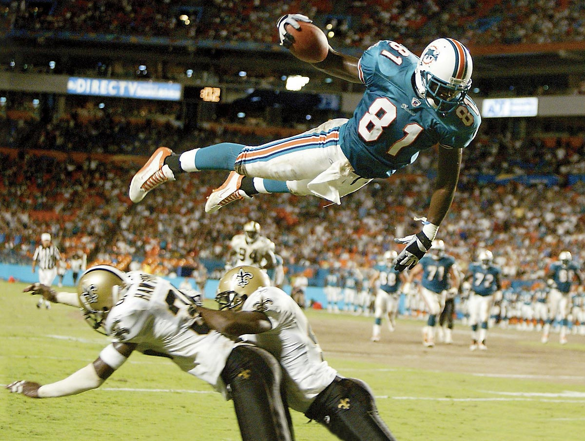 Saints at Dolphins, Aug. 15, 2002 | Dolphins tight end Randy McMichael soars over Saints defenders Michael Hawthorne (left) and Mel Mitchell to score a touchdown during a preseason game. The rookie tight end started all 16 games and caught 39 passes for 485 yards and four TDs during the season.
