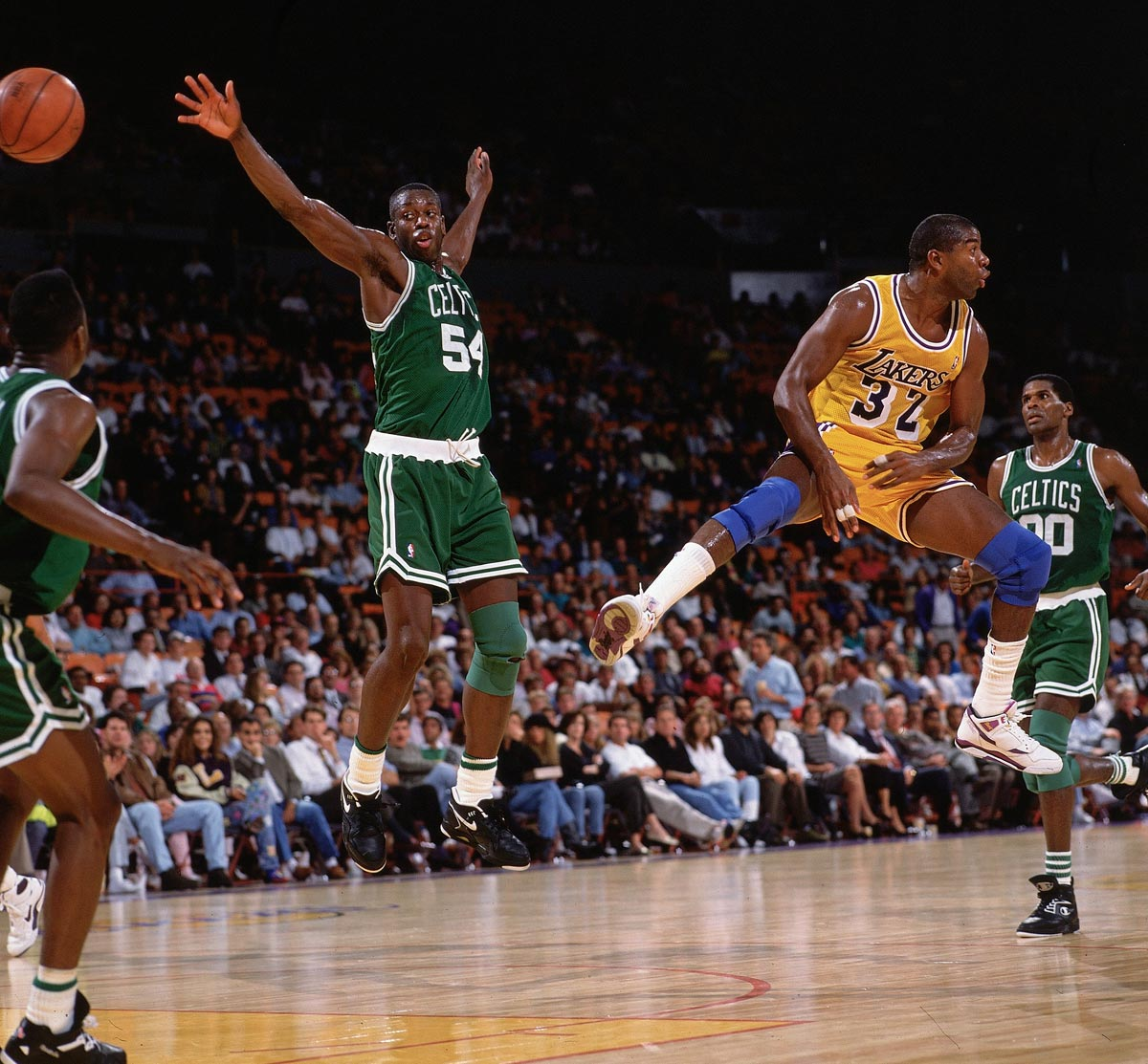 Lakers vs. Celtics, Oct. 22, 1991 | Lakers point guard Magic Johnson tosses a no-look pass past Celtics forward Ed Pinckney during a preseason game. About two weeks later, Johnson announced he was HIV-positive and retiring from basketball.