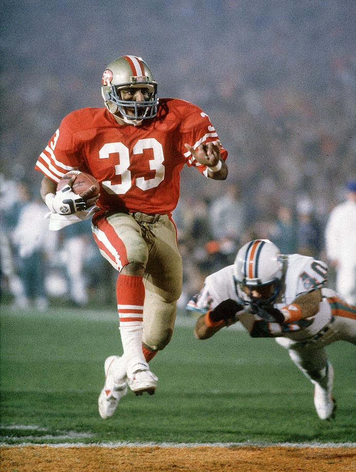 San Francisco 49ers running back Roger Craig rushes past diving Miami Dolphins defensive back Mike Kozlowski for a touchdown in his team's 38-16 win. Craig became the first player to score three touchdowns in a Super Bowl, catching two and rushing for a third.
