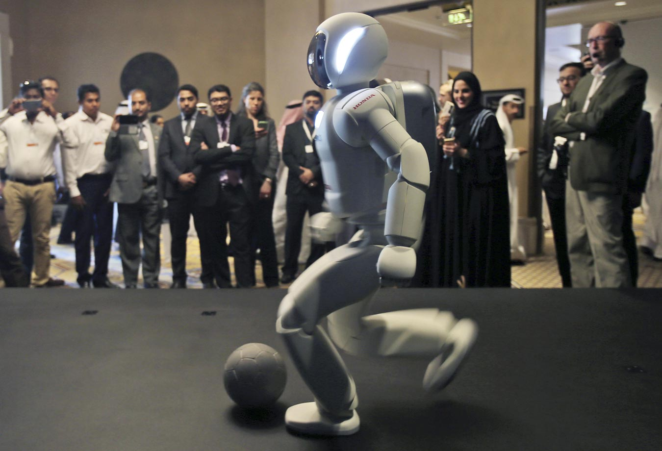A humanoid robot designed and developed by Honda and named Asimo plays football for the audience at the end of the company's presentation during the last day of the Government Summit in Dubai.