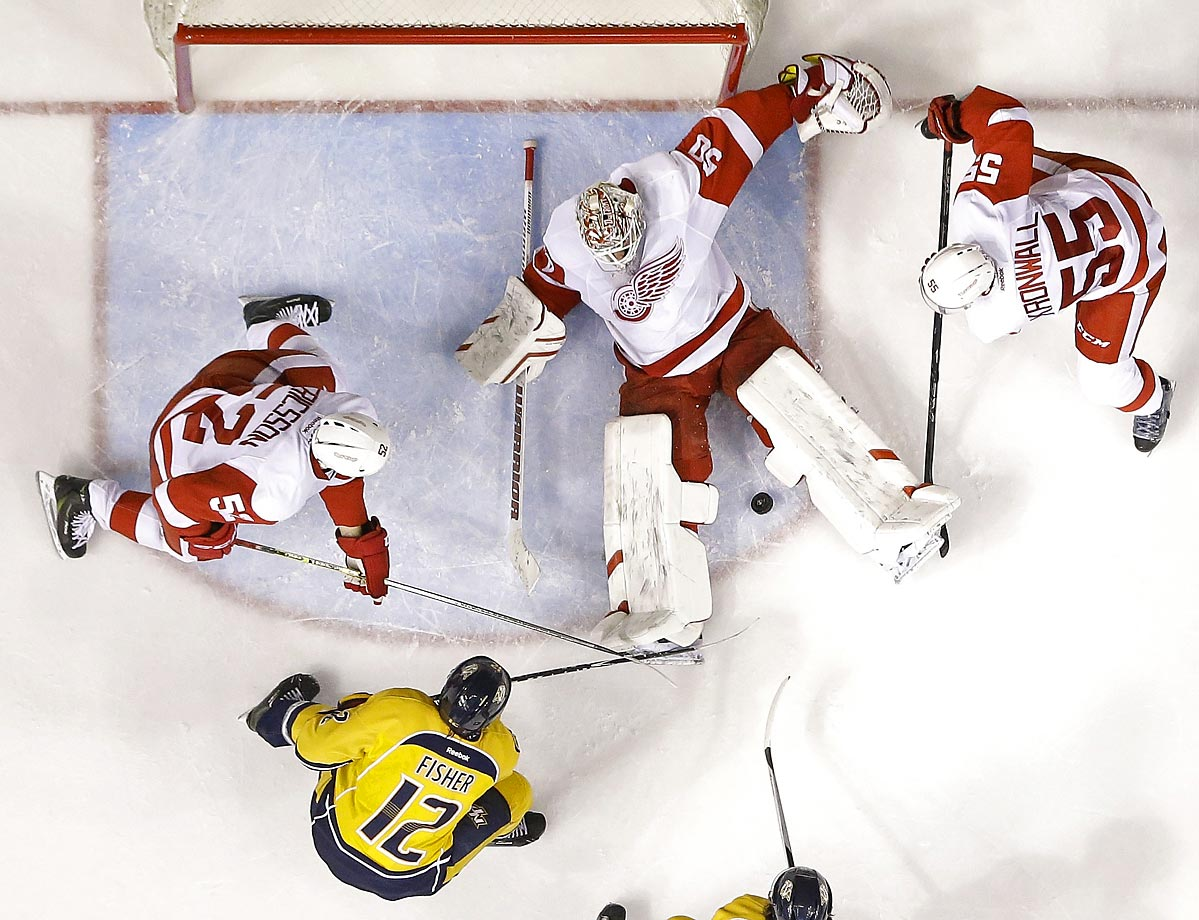 Detroit Red Wings goalie Jonas Gustavsson (50) covers up the puck as Nashville Predators forward Mike Fisher (12) tries to get past defenders Jonathan Ericsson (52) and Niklas Kronwall (55).