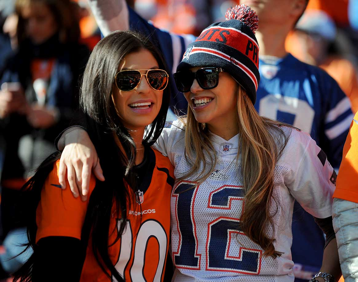 A Denver Broncos fan and New England Patriots fan look on before the AFC Championship game.