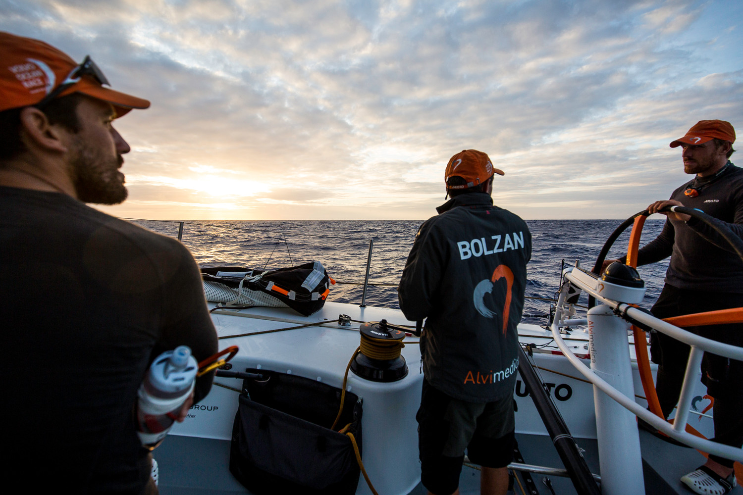 Mark Towill, Alberto Bolzan, and Dave Swete converse on deck as the sun sets on their watch.