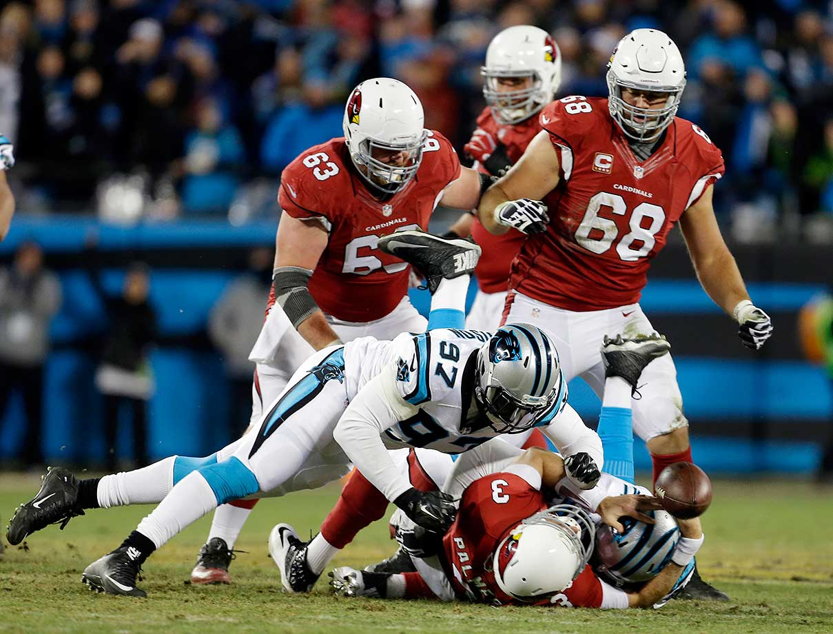 Carson Palmer fumbles as he is hit by Kawann Short and Mario Addison (97).